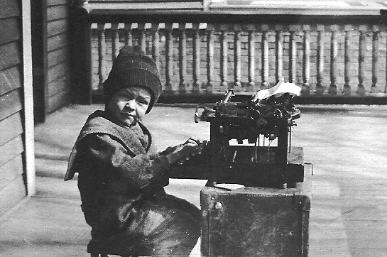 A vintage image of a young boy typing.